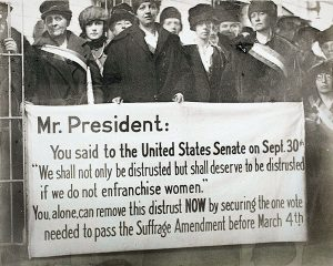 Women standing with poster to Mr. President asking for suffrage